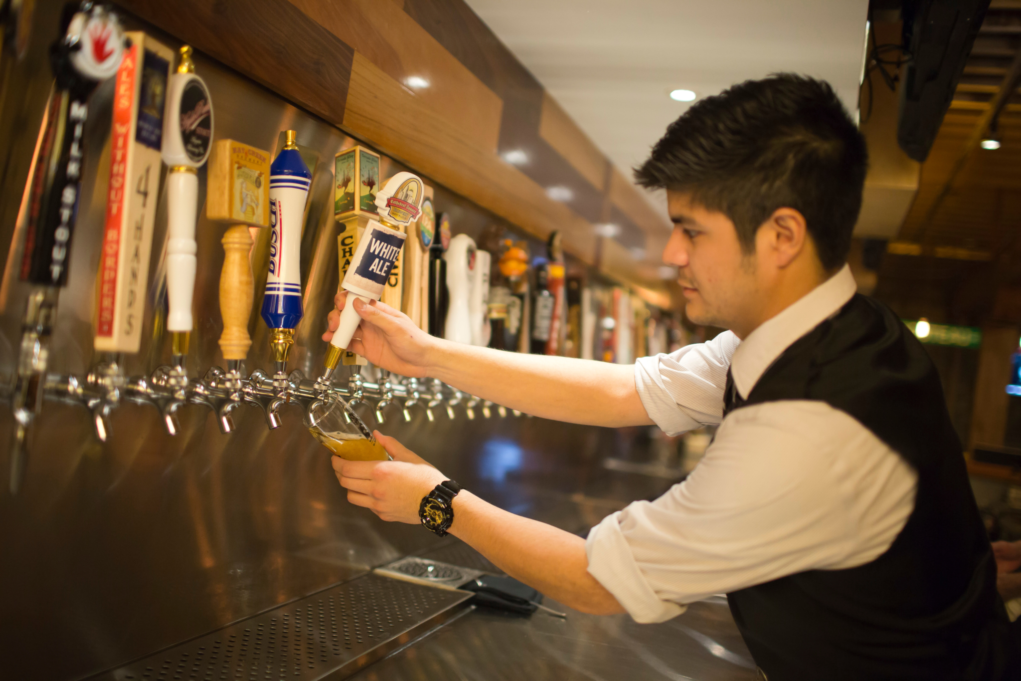 employee at 21st street brewers bar pouring a draft beer